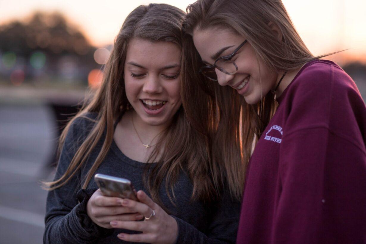 twee tieners kijken op hun mobiel